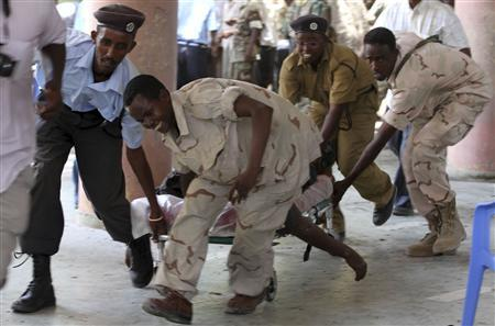 Soldiers carry the body of the chairman of Somali football federation Said Mugabe after an explosion at the national theatre in Mogadishu April 4, 2012. REUTERS/Omar Faruk