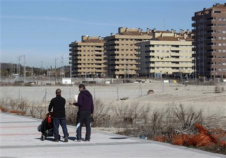People walk near almost empty apartment blocks in the Madrid satellite town of Sesena, February 23, 2012. REUTERS/Andrea Comas