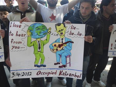 Demonstrators hold up a sign during a protest against Syria's President Bashar Al-Assad in Kafranbel, near Idlib April 3, 2012. REUTERS/Raad Al Fares/Shaam News Network/Handout