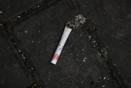 A cigarette stained with lipstick is seen left on the ground in Shanghai, March 22, 2012. REUTERS/Aly Song
