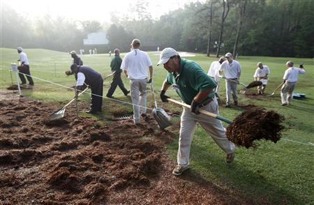 Members of the grounds crew clean debris off the course at the Augusta National Golf Club following an overnight storm as they prepare for the day's practice round at the 2012 Masters Golf Tournament in Augusta, Georgia, April 4, 2012. REUTERS/Mike Segar