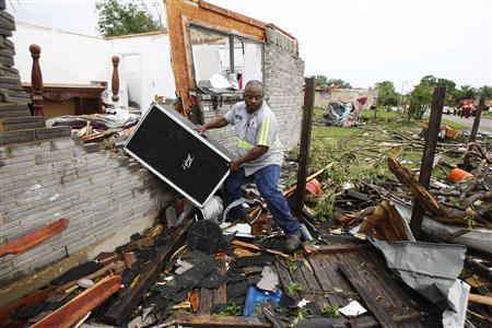Jason Moffett moves belongings out of a house which was destroyed after a series of tornadoes ripped through the Dallas suburb of Lancaster, Texas, April 3, 2012. REUTERS/Tim Sharp