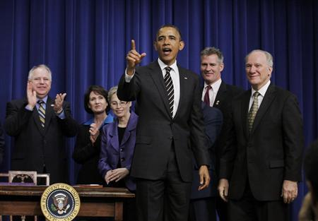 U.S. President Barack Obama points to the audience after signing the Stop Trading on Congressional Knowledge (STOCK) Act in the Eisenhower Executive Office building near the White House in Washington, April 4, 2012. REUTERS/Jason Reed