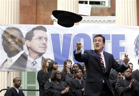 Actor and television host Stephen Colbert throws a hat into the crowd which belonged to former Republican Presidential candidate Herman Cain during a rally at the College of Charleston, South Carolina, January 20, 2012. The South Carolina Primary will be held on January 21. REUTERS/Jason Reed