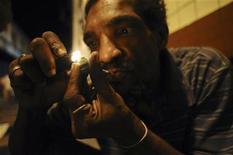 Наркоман курит крэк в Сальвадоре, 19 марта 2012 года. Когда на Сан-Паулу опускается ночь, на улицах города начинается торговля, которая никак не вяжется с образом Бразилии, старательно создаваемым на международной арене.  REUTERS/Lunae Parracho