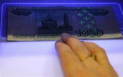 Работница банка в Санкт-Петербурге проверяет купюру, 4 февраля 2010 года. Рубль стабилен к бивалютной корзине в начале торгов четверга на фоне растущих нефти и сырьевых валют, но одновременно отрицательной динамики внешних фондовых рынков, дорожает к доллару США и дешевеет к евро, отыгрывая текущий рост пары евро/доллар. REUTERS/Alexander Demianchuk