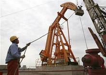 Рабочий контролирует процесс добычи нефти в уезде Шаньшань (КНР), 24 июля 2008 года. Китайская нефтяная компания PetroChina Co Ltd ведет переговоры с Royal Dutch Shell и Hess Corp о добыче нефти из битуминозных сланцев в бассейне Саньтанху в северо-западной провинции Синьцзян, сообщила материнская компания PetroChina, China National Petroleum Corp (CNPC). REUTERS/Stringer