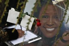 Женщина пишет послание в память о Уитни Хьюстон около входа на кладбище города Ньюарк (Нью-Джерси), 17 февраля 2012 года. Уитни Хьюстон утонула в очень горячей воде под воздействием кокаина, а рядом был найден белый порошок, говорится в финальном заключении коронера Лос-Анджелеса. REUTERS/Eduardo Munoz