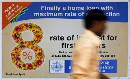 A man walks past a bank advertisement for housing loans in Mumbai March 22, 2010. REUTERS/Arko Datta/Files