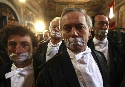 Lawyers protesting against planned reforms to Italy's legal system stand with tape over their mouths during a demonstration at the start of the judicial year in Naples, in this file photo taken January 28, 2012. REUTERS/AGN Foto/Files