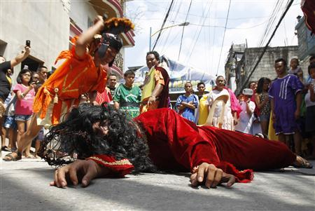 Richard Borja, 30, portraying Jesus Christ, is whipped by a man portraying a Roman soldier during ahead of Good Friday in Mandaluyong city, metro Manila April 5, 2012. REUTERS/Romeo Ranoco