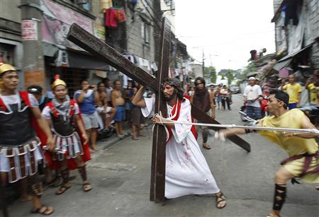 J.R. Galvez, 30, portraying Jesus Christ, carries a wooden cross while he is whipped by a man portraying a Roman soldier during a procession ahead of Good Friday in Mandaluyong city, metro Manila April 5, 2012. REUTERS/Romeo Ranoco