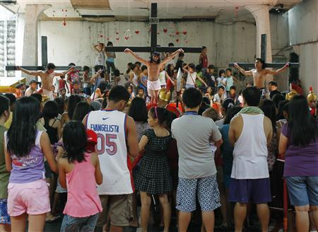 J.R. Galvez, 30, portraying Jesus Christ is crucified on a cross with men portraying thieves Dismas and Gestas as part of a voluntary ritual to mark the death of Christ ahead of Good Friday in Mandaluyong city, metro Manila April 5, 2012. REUTERS/Romeo Ranoco