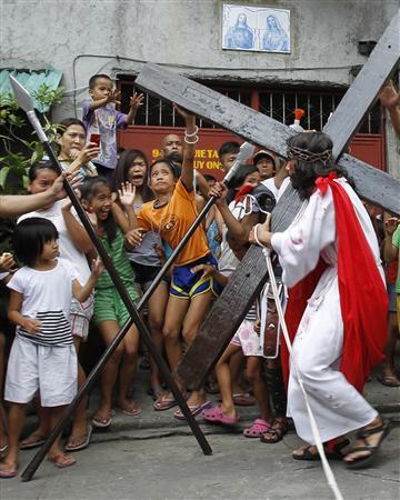 J.R. Galvez, 30, portraying Jesus Christ, carries a wooden cross during a procession ahead of Good Friday in Mandaluyong city, metro Manila April 5, 2012. REUTERS/Romeo Ranoco