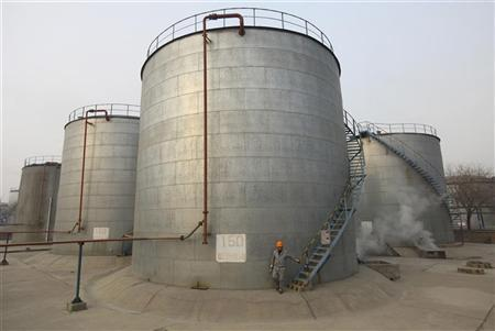 An employee walks down the stairs of an oil storage tank after a regular check at a PetroChina refinery in Lanzhou, Gansu province January 7, 2011. REUTERS/Stringer