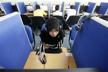 A woman browses the Internet at a cyber cafe in Putrajaya June 16, 2011. REUTERS/Bazuki Muhammad/Files
