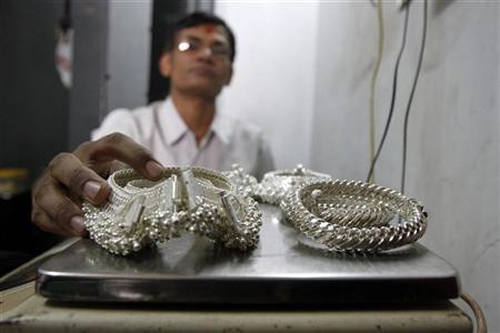 A silver trader weighs his silver ornaments inside his shop in Ahmedabad April 27, 2011. REUTERS/Amit Dave/Files