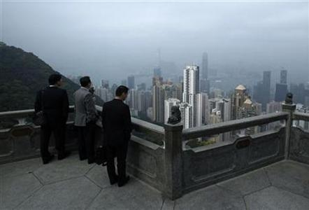 Businessmen at the Peak look at high-rise residential and commercial towers in Hong Kong March 14, 2012. REUTERS/Bobby Yip/Files