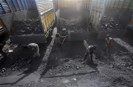 Labourers load coal onto trucks at a coal yard on the outskirts of Jammu March 23, 2012. REUTERS/Mukesh Gupta