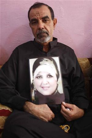 The husband of Shaima Alawadi, Qassim Rzooqi, holds the picture of his slain wife at her father's house in Samawa, 270 km (160 miles) south of Baghdad, April 1, 2012. REUTERS/Atef Hassan