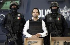 "Federal police escort drug suspect Jose Antonio Acosta Hernandez, ""El Diego"", as he is presented to the media during a news conference at the federal police headquarters in Mexico City July 31, 2011. REUTERS/Carlos Jasso"