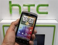 Мужчина держит смартфон HTC в магазине в Тайбэй, 6 апреля 2012 года. Чистая прибыль тайваньского производителя смартфонов HTC Corp в первом квартале 2012 года упала на 70 процентов, однако компания ожидает роста продаж после выпуска новой серии One, запланированного на этот месяц. REUTERS/Shengfa Lin
