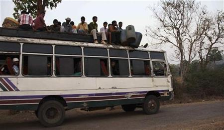 Tribal villagers sit atop of a bus as they travel through the remote district of Kandhamal in Orissa March 18, 2012. REUTERS/Stringer/Files