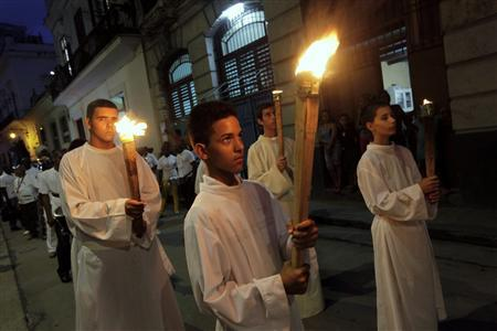 Altar boys hold torches during a Via Crucis (Way of the Cross) procession on Good Friday in Havana April 6, 2012. Bells rang from Roman Catholic churches throughout Havana on Friday to remember the death of Jesus Christ as Cubans celebrated a holiday on Good Friday for the first time in more than half a century. The day off, granted at the request of Pope Benedict on his recent visit to the communist island, translated into quieter streets than usual, but only sparse attendance at a Mass in the city's main cathedral presided over by Cardinal Jaime Ortega. REUTERS/Enrique de la Osa