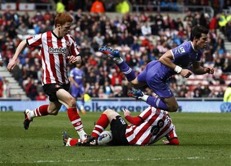 Tottenham Hotspur's Gareth Bale (R) falls forward through the air from the tackle of Sunderland's Craig Gardner (C) during their English Premier League soccer match at the Stadium of Light in Sunderland, England April 7, 2012. REUTERS/David Moir