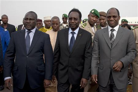 Mali's interim President Diouncounda Traore (C), flanked by Burkina Faso's Foreign Minister Djibril Bassole (R) and Ivory Coast's Minister of African Integration Adama Bictogo, arrives at Bamako airport after Mali's military junta agreed to hand over power to a civilian government led by Traore April 7, 2012. REUTERS/Joe Penney