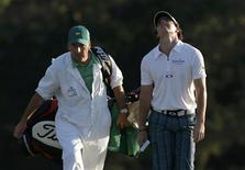 Rory McIlroy of Northern Ireland (R) walks with caddie J.P. Fitzgerald onto the 18th green during third round play in the 2012 Masters Golf Tournament at the Augusta National Golf Club in Augusta, Georgia, April 7, 2012. REUTERS/Phil Noble