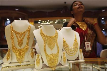 A saleswoman displays a gold necklace at a jewellery showroom in Kolkata August 1, 2011. REUTERS/Rupak De Chowdhuri/Files