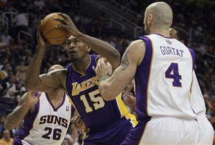 Los Angeles Lakers forward Metta World Peace (15) drives to the basket against the Phoenix Suns' Shannon Brown (26) and Marcin Gortat during their NBA basketball game in Phoenix, Arizona, April 7, 2012. REUTERS/Darryl Webb