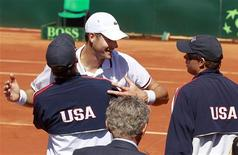 John Isner (C) of the U.S is congratulated by the U.S. Davis Cup doubles team Bob (R) and Mike Bryan after winning against France's Jo-Wilfried Tsonga during his Davis Cup quarter-final tennis match at the Monaco Country Club in Roquebrune Cap Martin April 8, 2012. REUTERS/Eric Gaillard