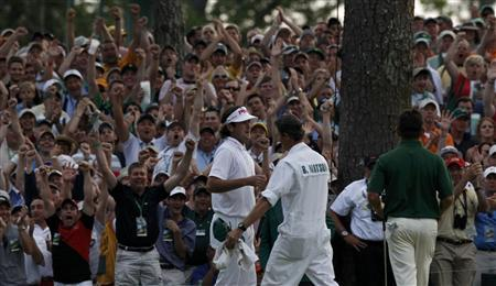 Bubba Watson of the U.S. (L) hugs his caddie Ted Scott (C) next to Louis Oosthuizen (R) of South Africa after winning the Masters during a playoff in the 2012 Masters Golf Tournament at the Augusta National Golf Club in Augusta, Georgia, April 8, 2012. REUTERS-Mike Segar