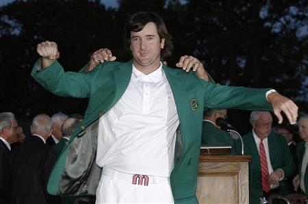 Bubba Watson of the U.S. receives his green jacket from 2011 champion Charl Schwartzel of South Africa after winning the 2012 Masters Golf Tournament at the Augusta National Golf Club in Augusta, Georgia, April 8, 2012. REUTERS/Mike Segar