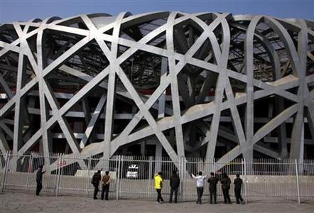 Chinese tourists look through a security fence at the National Stadium, also known as the ''Bird's Nest'', which was the venue for the athletics and the opening and closing ceremonies of the 2008 Olympic Games in Beijing March 23, 2012. REUTERS/David Gray