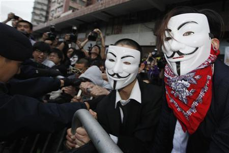 Pro-democracy demonstrators wearing Anonymous masks, scuffle with police during a protest against the Chinese government's meddling into the Hong Kong's chief executive election, in Hong Kong April 1, 2012. REUTERS/Tyrone Siu