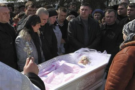 People stand near the coffin of Oksana Makar during a funeral ceremony in the settlement of Shevchenkovo outside the town of Mykolayiv in southern Ukraine March 31, 2012. REUTERS/Yevgeny Volokin
