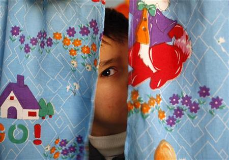 An autistic child peers from between curtains at the Consulting Centre for Autism in Amman, March 30, 2010, one of the few places in the country that helps children with the condition. REUTERS/Ali Jarekji