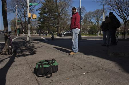 A man looking for work stands next to a bag of tools at a street corner in Brooklyn, New York on April 3, 2012. REUTERS/Eduardo Munoz