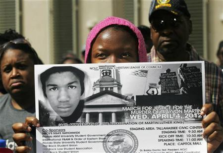 A young participant watches a speaker from behind a sign during a rally organized by the National Christian League of Councils for slain teen Trayvon Martin in Tallahassee, Florida April 4, 2012. REUTERS/Philip Sears