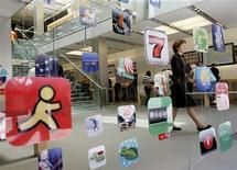 Женщина выходит из магазина Apple в Сан-Франциско, в котором развешены логотипы приложений для гаджетов Apple, 22 апреля 2009 года. Поделить счет в ресторане или совместные расходы на поездку теперь станет намного проще: для этого достаточно стукнуть одним телефоном по корпусу другого. REUTERS/Robert Galbraith/Files