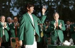 Bubba Watson of the U.S. (L) waves while wearing his green jacket after winning as Augusta National Golf Club Chairman William Porter Payne (R) applauds after the 2012 Masters Golf Tournament at the Augusta National Golf Club in Augusta, Georgia, April 8, 2012. REUTERS/Phil Noble