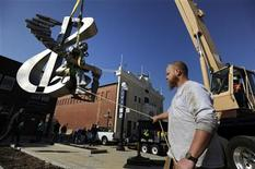 Workers install a statue of jazz great Duke Ellington on a pedestal in a newly-constructed plaza near the historic Howard Theater in Washington, March 29, 2012. REUTERS/Jonathan Ernst