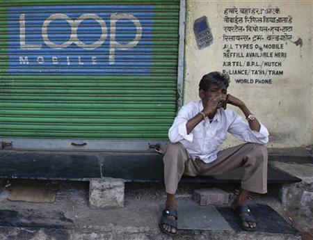 A man smokes in front of a closed shop displaying the Loop mobile logo on its shutter in Mumbai February 2, 2012. REUTERS/Danish Siddiqui/Files