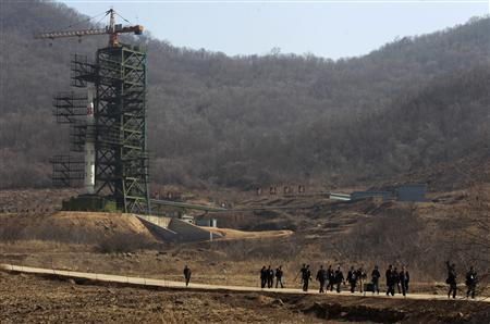 Journalists leave in front of the Unha-3 (Milky Way 3) rocket is pictured sitting on a launch pad at the West Sea Satellite Launch Site, during a guided media tour by North Korean authorities in the northwest of Pyongyang April 8, 2012. REUTERS/Bobby Yip