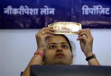 A bank employee checks a 500 rupee note at a counter in Mumbai October 25, 2008. REUTERS/Punit Paranjpe/Files
