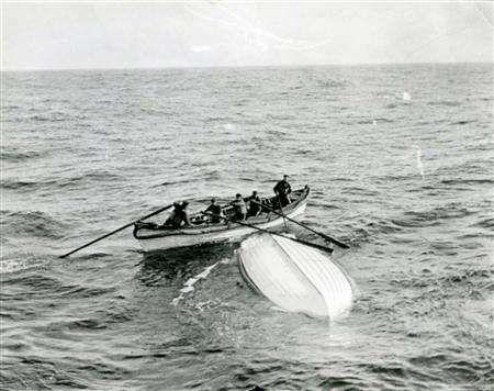 A boat from the ship MacKay-Bennett examines an overturned lifeboat from the Titanic in waters of the Atlantic in 1912. REUTERS/Courtesy of Dalhousie University Archives and Special Collections, Halifax, N.S. Thomas Head Raddall Fonds/Handout