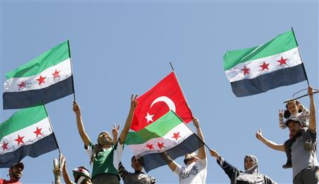 Syrian refugees wave Turkish (C) and Syrian Independence flags during a protest against Syria's President Bashar al-Assad at Yayladagi refugee camp in Hatay province on the Turkish-Syrian border April 10, 2012. REUTERS-Umit Bektas